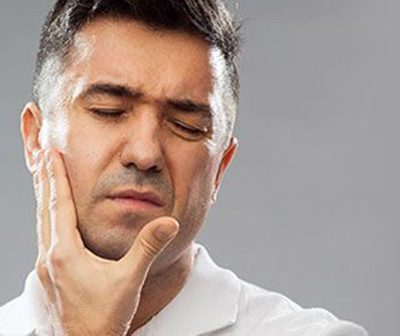 Brunette man holding the right side of his face, perhaps for a dental emergency