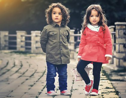 Young boy and girl standing on a brick bridgewalk