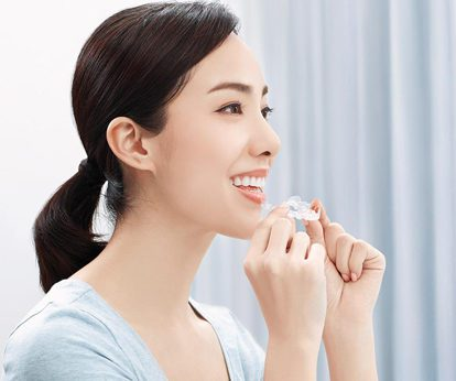 Asian woman with a ponytail putting on an Invisalign aligner